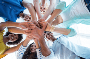people with hands in showing teamwork